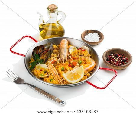 Spanish paella with shrimp and mussel served with olive oil and spices isolated on white background.