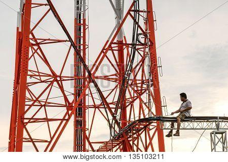 PATTAYA, THAILAN - 20 JUN - Dunidentified engineer repairing maintenance telecommunication tower in evening at Pattaya city, Thailand in June 20, 2016