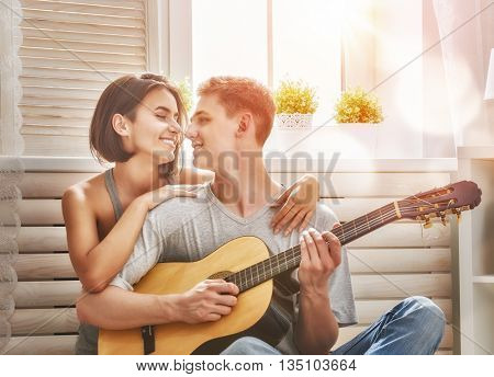 Happy couple in love. Stunning sensual portrait of young stylish fashion couple indoors. Young man playing guitar for his beloved girl.