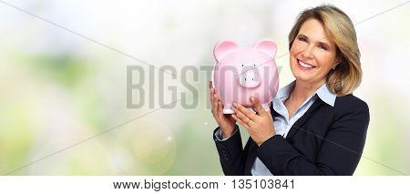 Senior business woman with a piggy bank.
