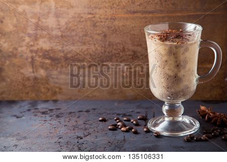 Brown smoothie of chocolate banana and milk coffee ice-cream cocktail on dark metal table with rusty brown background copy space