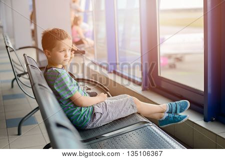 Boy Sitting With His Luggage At Airport