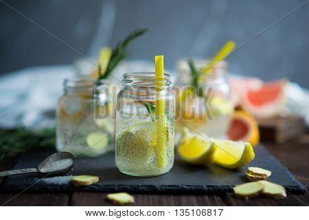 Lemonade with fresh lemons, grapefruit and rosemary in glass jars on a dark stone