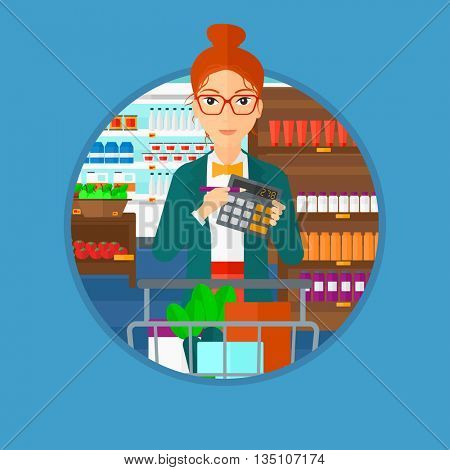 Woman at the supermarket with calculator and supermarket trolley full with products. Woman checking prices with calculator. Vector flat design illustration in the circle isolated on background.