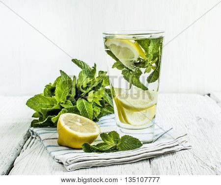 detox water with lemon and mint in a glass on a background of leaves of mint and strawberries on a wooden table closeup