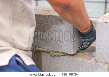 builder puts a cinder block for the construction of the building. skillful hands puts a brickwall. cinder blocks