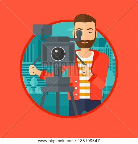 A hipster cameraman with the beard looking through movie camera on a tripod. Young man with professional video camera in the city. Vector flat design illustration in the circle isolated on background.