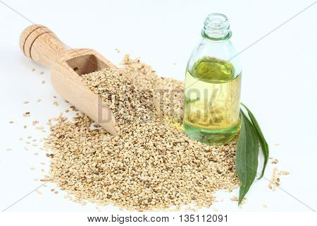 Organic unpeeled white sesame seeds and sesame oil. White sesame seeds in wooden spoon. Sesame seeds and oil on white background.