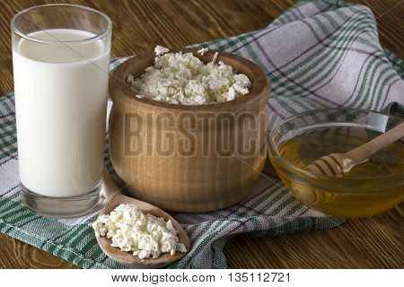 Honey, cottage cheese and glass with milk on wooden background