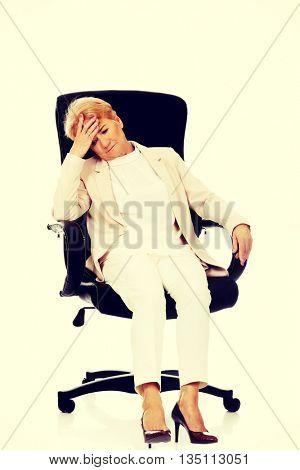 Worried elderly business woman sitting on armchair