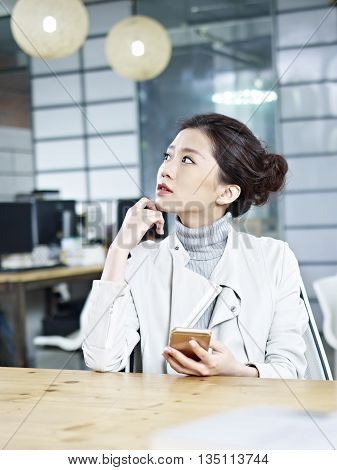 young asian business woman sitting in office looking up thinking with cellphone in hand.