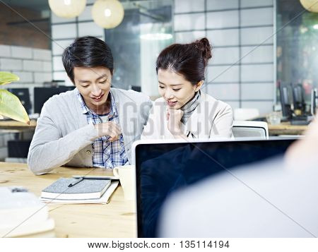 young asian business man and woman working together using tablet computer in office.