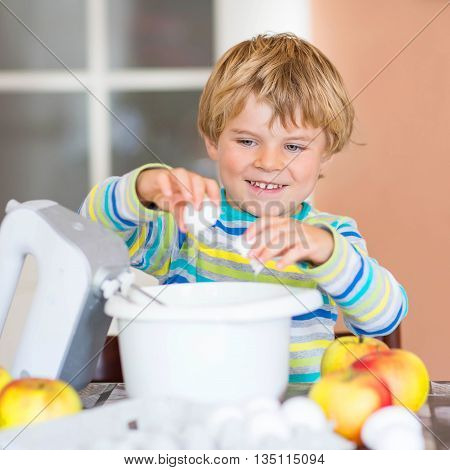Cute funny blond kid boy of 4 years baking apple cake in domestic kitchen. Happy child having fun with working with mixer, flour, eggs and fruits.
