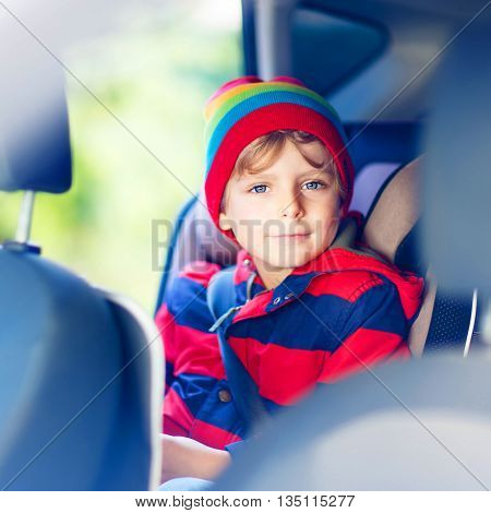 Portrait of preschool little kid boy sitting in car. Child in safety car seat with belt. Safe travel with kids and traffic laws concept.