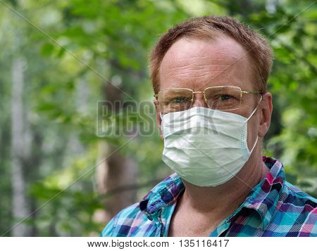 Portrait of a man with glasses and a medical mask. Background nature a lot of greens - the grass the trees. Concept - an allergy in the spring summer. Summer's disease - an allergy common cold