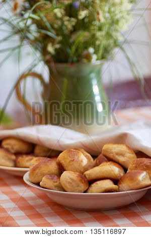 Traditional latvian bacon pies and meadow herbs background. Rustic style.