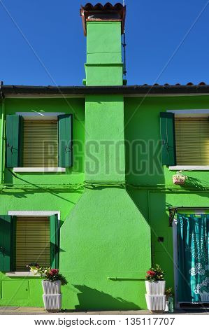 Green facade of the colorful house on the famous island Burano. Venice and the Venetian lagoon are on the UNESCO World Heritage List