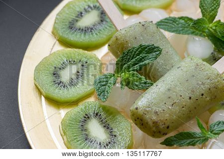 Kiwi sorbet ice cream popsicles on golden plate with ice cubes chopped kiwi slices and mint leaves on a black background. Kiwi sorbet ice cream popsicles. Horizontal. Close.