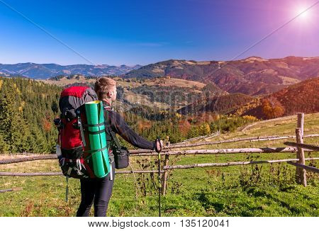 Hiker with Backpack and Walking Pole Standing on Grassy Meadow Observing Mountains Scenery of Autumnal Colorful Forest