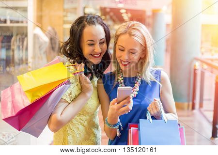 Two women looking at the smartphone while shopping
