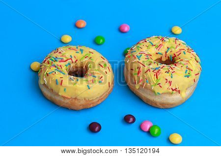 top view of two donuts on blue background
