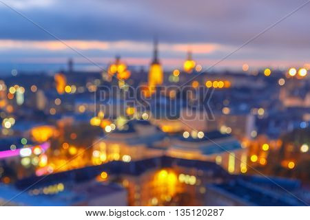 Out-of-focus shimmering city background, blurred bokeh photo of old town at sunset, Tallinn, Estonia