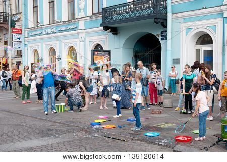 SAINT - PETERSBURG, RUSSIA - JUNE 20, 2016: Children blow giant soap bubbles outdoor near Griboyedov Channel not far from Nevsky Avenue in St Petersburg