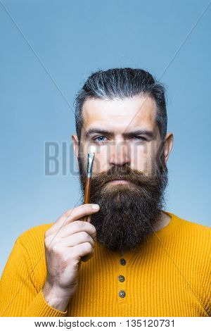 handsome bearded man with long lush beard and moustache on serious face holding painting brush in yellow shirt in studio on blue background