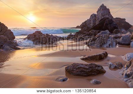 Fantastic big rocks and ocean waves at golden sundown time, Portugal