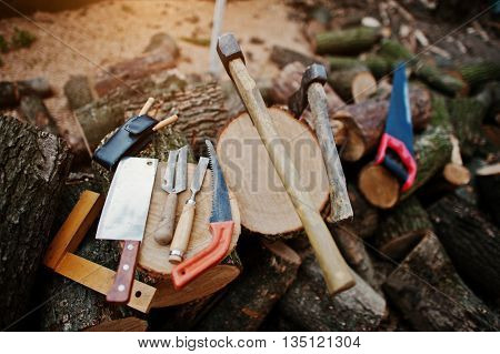 Two Axes In Stumps With Wood Working Tools Background Chopped Firewood.