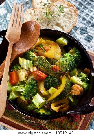 Tasty Colorful Vegetables Ragout with Zucchini Carrots Broccoli Leek and Red Bell Pepper in Black Iron Stewpot with Wooden Spoon and Fork and Bread with Thyme closeup on Blue Napkin