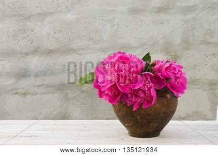 bouquet of pink peony in an old clay pot on a light blurred background
