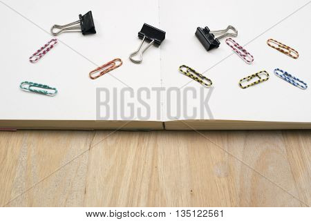 paper clips on a notebook and wood background