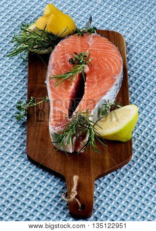 Perfect Raw Salmon Steak with Lemon Rosemary and Thyme on Wooden Cutting Board closeup on Blue Napkin background