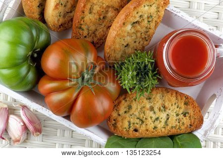 Tomato Juice in Glass Jar with Raw Tomatoes Crispy Bread and Fresh Herbs closeup into White Wooden Tray. Top View on Wicker background