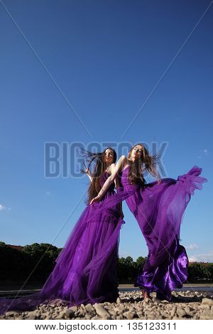 young pretty women with long windy hair in elegant violet dresses standing on stony ground sunny day on blue sky background