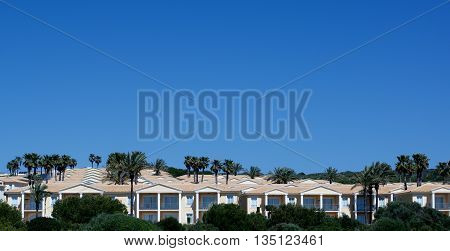 Luxury Residential District with New Modern and Elegant Houses between Green Palm Trees closeup on Blue Sky background Outdoors
