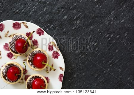 Delicious chocolate tartlets with one cherry, chocolate and coconut on slate background