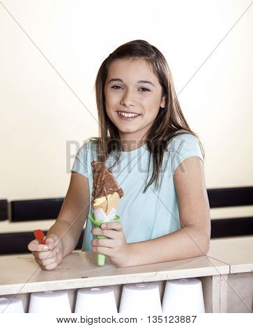 Smiling Girl Holding Chocolate Ice Cream Cone At Counter