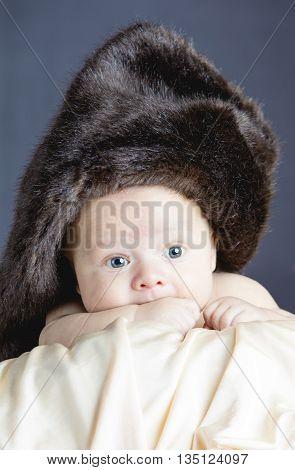 Newborn Boy with sparkling eyes wearing wool hat on bright blanket
