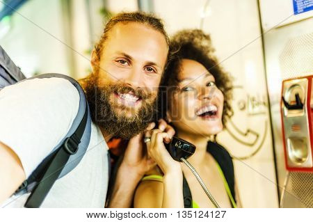 The young couple using payphones in street