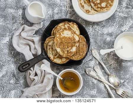 Whole grain pancakes in a cast iron pan on a stone background. Breakfast table