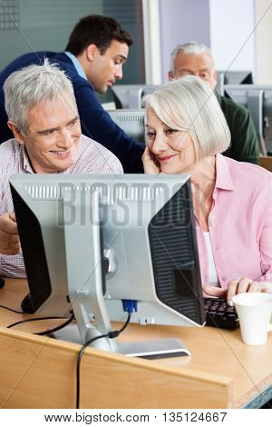 Happy Senior Classmates Using Computer At Classroom