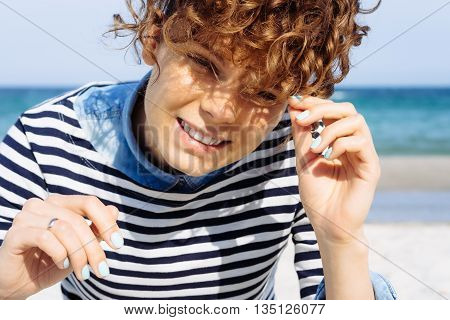 Portrait of laughing pretty girl with curly brown hair on the beach which is looking into the camera in bright sunlight