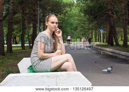 Young Woman In A Striped Dress Sitting