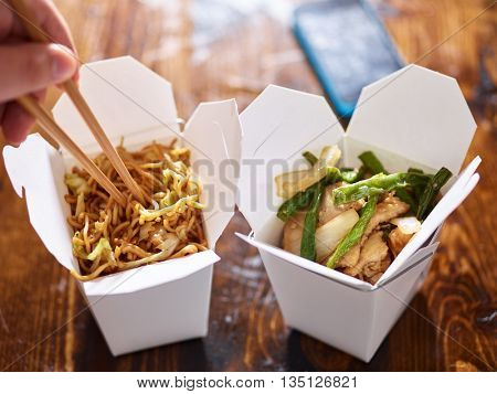 eating lo mein out of chinese take out box wih chopsticks