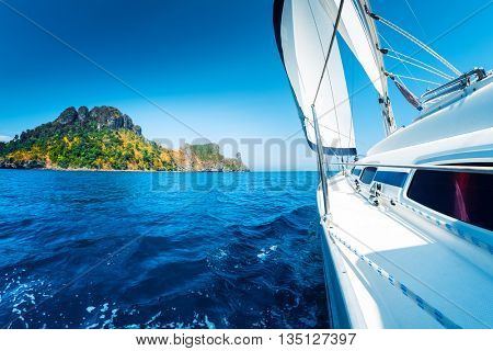 Sailing vessel moving in the sea with island on the background