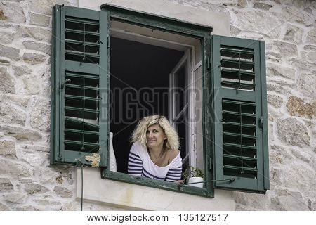 Beautiful blonde woman is looking out the window leaning on the windowsill