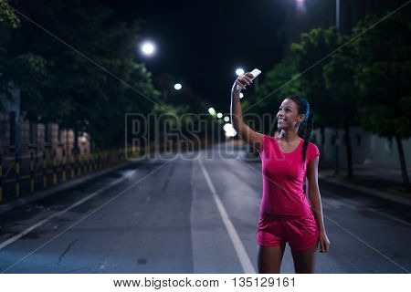 Young sportswomen making a selfie outdoors in the city.