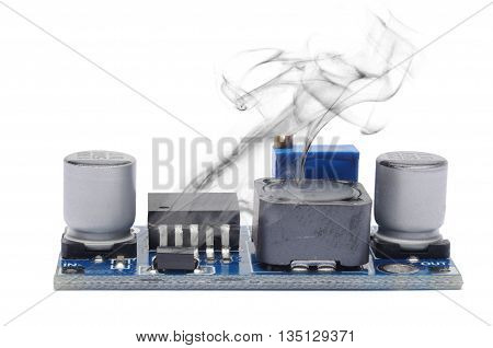 The electronic voltage stabilizer smokes from overheating. Isolated on white.